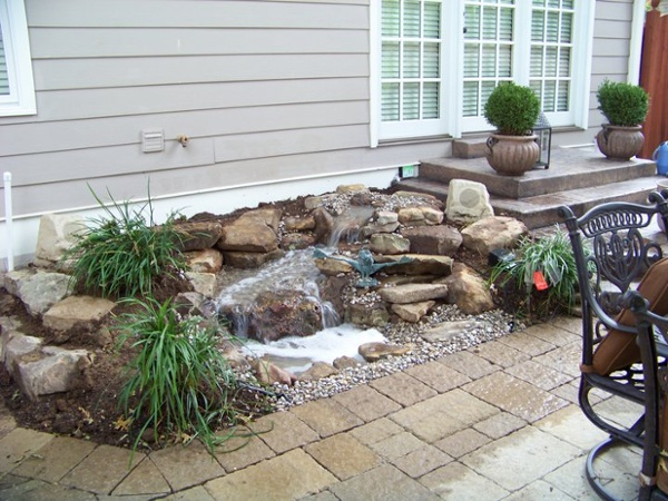 Along side this patio the homeowner has a 5-6ft Pond-Less stream that adds just the right amount of water for quaint sounds, night time interest and bird watching from the nearby windows.